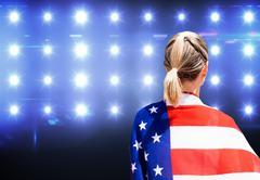 American sportswoman is posing against composite image of blue spotlight - stock photo
