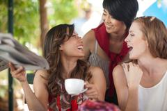 Three female friends laughing together at sidewalk cafe in city Stock Photos