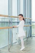 Little ballerina girl. Adorable child dancing classical ballet in a white studio Stock Photos