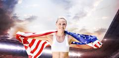 Composite image of portrait of smiling sportswoman posing with an american fl - stock photo