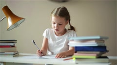 Schoolgirl doing homework and preparing for exams, cute children learning her - stock footage