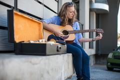Female street musician sitting on ledge, tuning guitar Stock Photos
