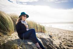Woman wearing felt hat and sunglasses sitting on dunes, Dillon Beach, Stock Photos