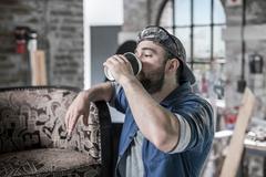 Worker in antique restoration workshop drinking takeaway coffee Stock Photos