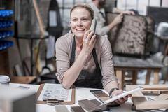 Craftswoman talking on smartphone in antique restoration workshop Stock Photos