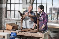 Senior craftsman demonstrating restoration to trainee in antique restoration Stock Photos