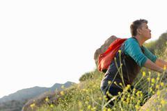Woman hiker climbing up hill Stock Photos