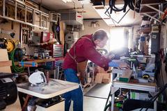 Senior man sawing with circular saw in carpentry workshop Stock Photos