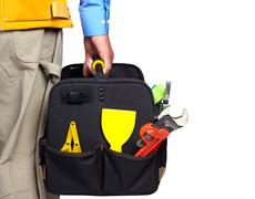 Hand of handyman with a tool bag. Stock Photos