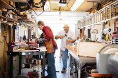 Senior men working with hammer in carpentry workshop Stock Photos