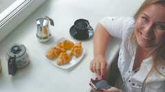 Young beautiful girl has breakfast listen to music use smartphone on a sunny day Stock Footage