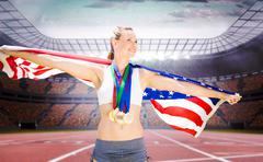 Portrait of happy sportswoman with medals holding american flag against a tra - stock photo