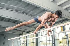 Male gymnast performing handstand on parallel bars Stock Photos