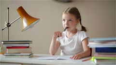 Girl learning lessons, cute girl making her homework, schoolgirl studing at home Stock Footage