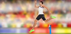 Male athlete running on track and jumping obstacles Stock Photos