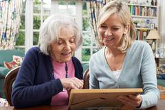 Senior Woman Looks At Photo Frame With Mature Female Neighbor Stock Photos
