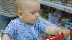 Little baby sitting in a grocery cart in a supermarket, while his father chooses Stock Footage