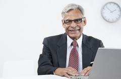Old businessman with a laptop Stock Photos