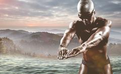 Swimmer ready to dive against trees and mountain range against cloudy sky Stock Photos