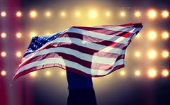 Composite image of rear view of sportsman posing with an american flag - stock photo