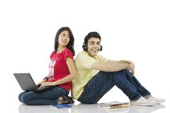 Girl sitting with a laptop while boy listens to music Kuvituskuvat