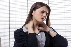 Businesswoman getting a neck ache Stock Photos