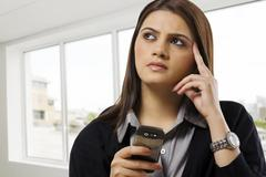 Businesswoman contemplating while holding a mobile phone Stock Photos