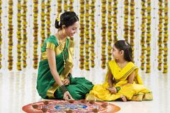 Woman arranging diyas on a rangoli Stock Photos