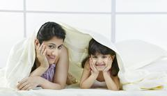 Portrait of mother and daughter under a bed sheet Stock Photos