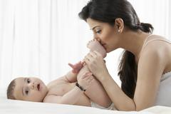 Mother kissing the baby's feet Stock Photos