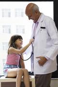 Girl checking a doctor's heartbeat Stock Photos