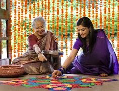 Mother and daughter making a rangoli Stock Photos