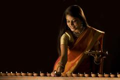 Woman arranging diyas Stock Photos