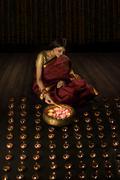 Woman lighting diyas Stock Photos