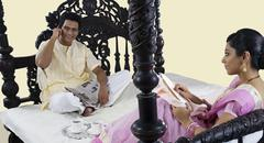 Bengali woman stitching while husband talks on a mobile phone Stock Photos