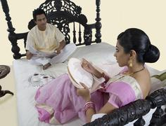 Bengali woman stitching while husband reads the newspaper Stock Photos