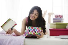 Girl smiling at the contents of a gift box Stock Photos