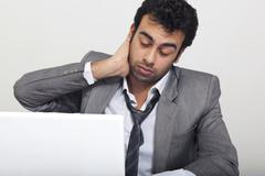 Businessman feeling tired at work Stock Photos