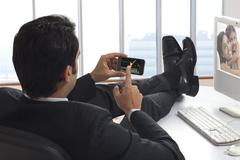 Businessman watching a video clip on his phone Kuvituskuvat