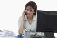 Angry businesswoman on call while using computer Stock Photos
