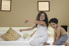 Brother and sister having fun on a bed Stock Photos