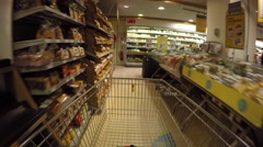 Pushing supermarket cart past thru aisles Stock Footage
