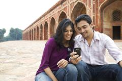 Couple reading an sms at Humayuns Tomb Stock Photos
