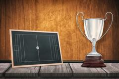 Focus on a trophy against black board on a wooden table - stock illustration