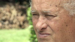pensive old man closeup portrait in the garden: thoughtful old man - stock footage