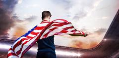 Composite image of rear view of sportsman holding an american flag - stock photo