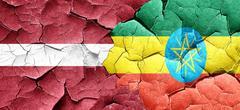 Latvia flag with Ethiopia flag on a grunge cracked wall Stock Illustration