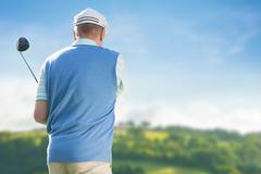 Man is playing golf against country scene Stock Photos
