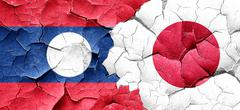 Laos flag with Japan flag on a grunge cracked wall - stock illustration