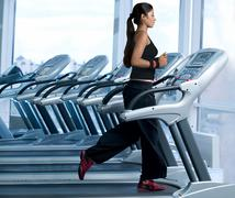 Woman running on a treadmill in a gym Stock Photos